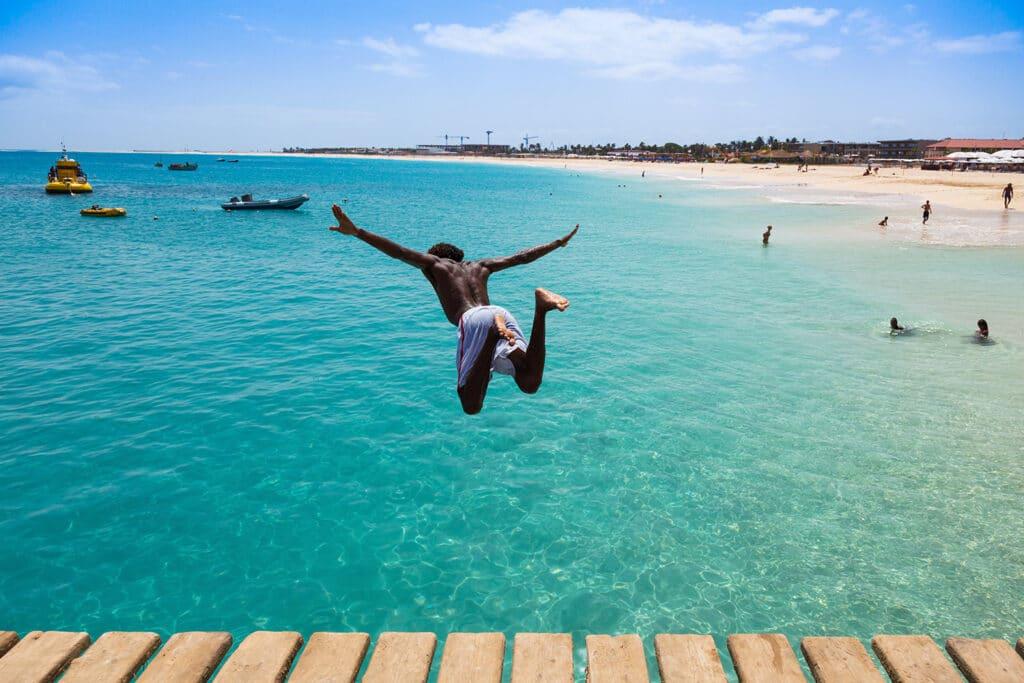 Jongen neemt een duik in de zee vanaf de pier in Santa Maria op het eiland Sal in Kaapverdië.